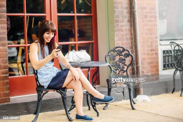 Caucasian woman using cell phone at sidewalk cafe