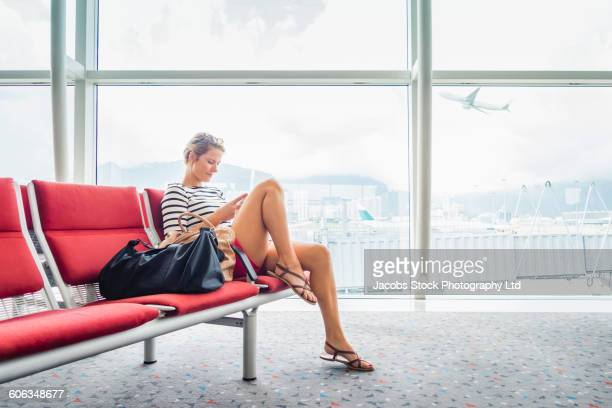 caucasian woman using cell phone in airport - wachten stockfoto's en -beelden