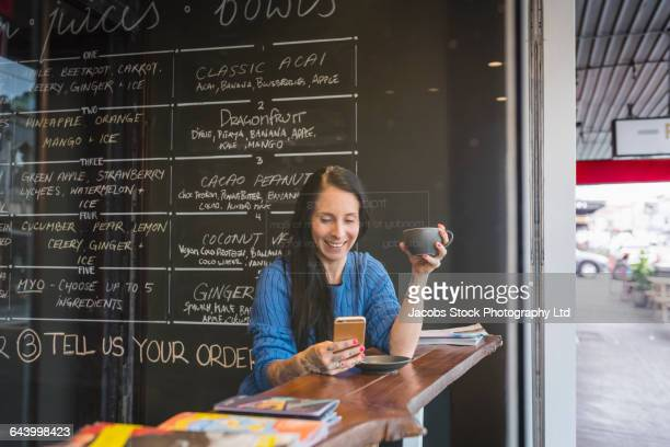 Caucasian woman using cell phone in cafe