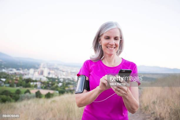 Caucasian woman using cell phone on hilltop