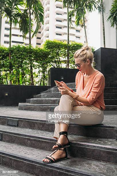 caucasian woman using cell phone on stairs - tropical tree stockfoto's en -beelden