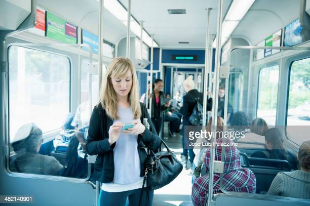 caucasian woman using cell phone on train - west new york new jersey - fotografias e filmes do acervo
