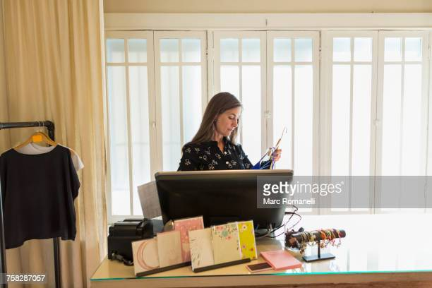 Caucasian woman using computer in clothing store