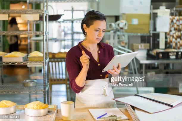 Caucasian woman using digital tablet in bakery