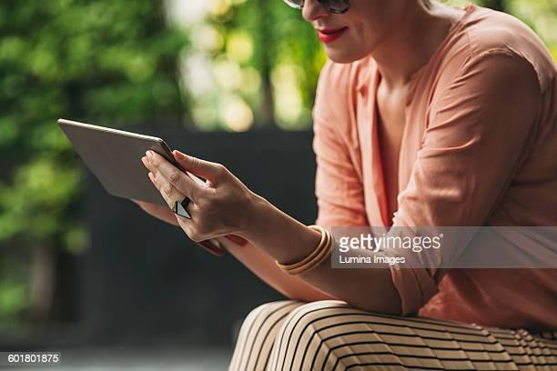 Caucasian woman using digital tablet outdoors