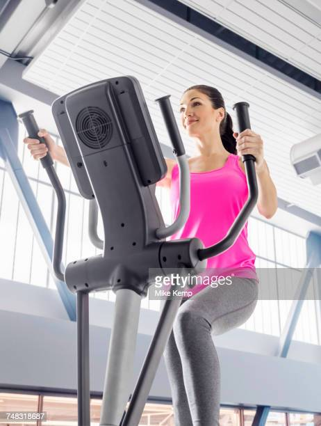 Caucasian woman using elliptical machine in gymnasium