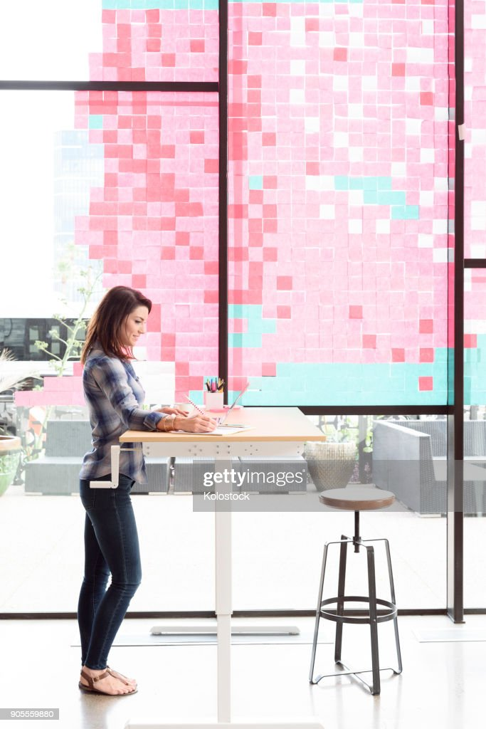 Caucasian woman using laptop at standing workstation : Stock Photo