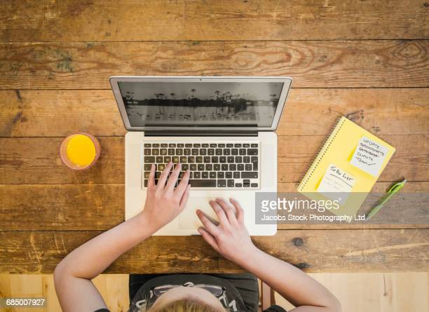 Caucasian woman using laptop at wooden table