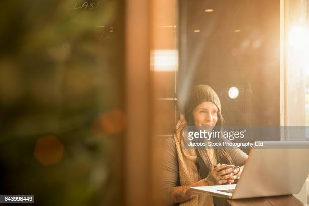Caucasian woman using laptop in cafe