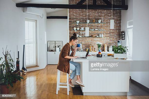 Caucasian woman using laptop in kitchen