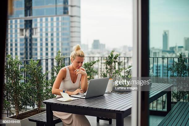 Caucasian woman using laptop on balcony