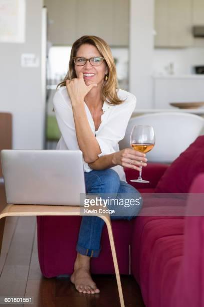 Caucasian woman using laptop on sofa
