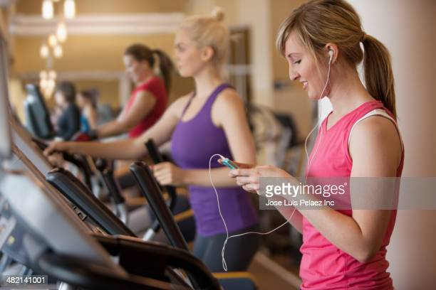 Caucasian woman using mp3 player on elliptical trainer in gym