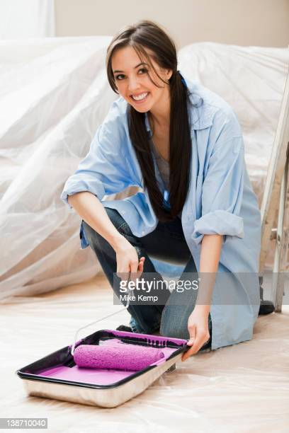 Caucasian woman using paint roller