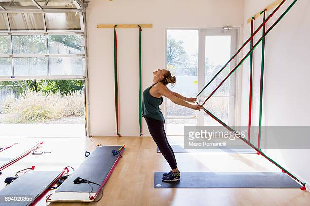 caucasian woman using resistance bands in gymnasium - open grave stock photos and pictures