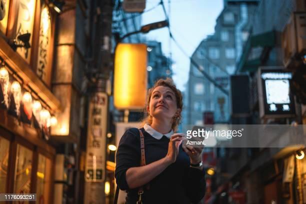 kaukasische frau mit smartphone, um tokio in der nacht zu navigieren - shinjuku bezirk stock-fotos und bilder