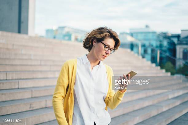 caucasian woman using smartphone outdoors - 40 44 years stock pictures, royalty-free photos & images
