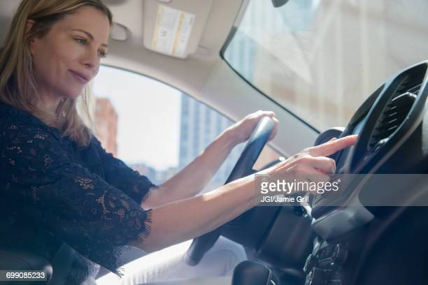Caucasian woman using touch screen on dashboard of car