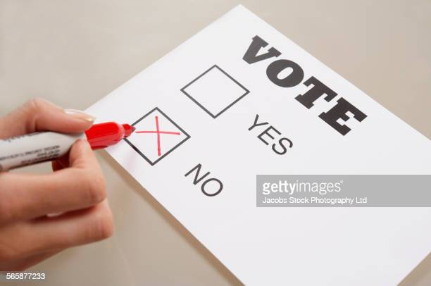 caucasian woman voting no on ballot - voter registration stock pictures, royalty-free photos & images