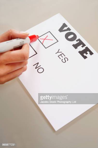 Caucasian woman voting yes on ballot