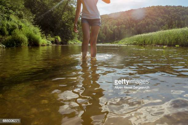 Caucasian woman wading in river
