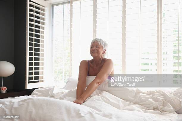 Caucasian woman waking in bed