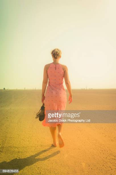 Caucasian woman walking barefoot in desert