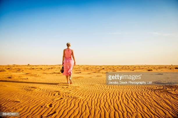caucasian woman walking barefoot in desert - hot arab women stock photos and pictures