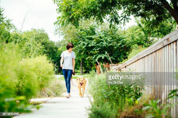 Caucasian woman walking dog in park
