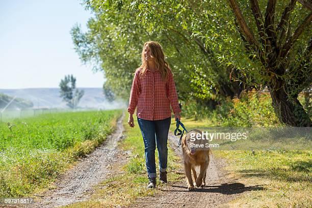 caucasian woman walking dog on dirt path - one animal stockfoto's en -beelden