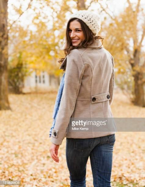 Caucasian woman walking in autumn leaves