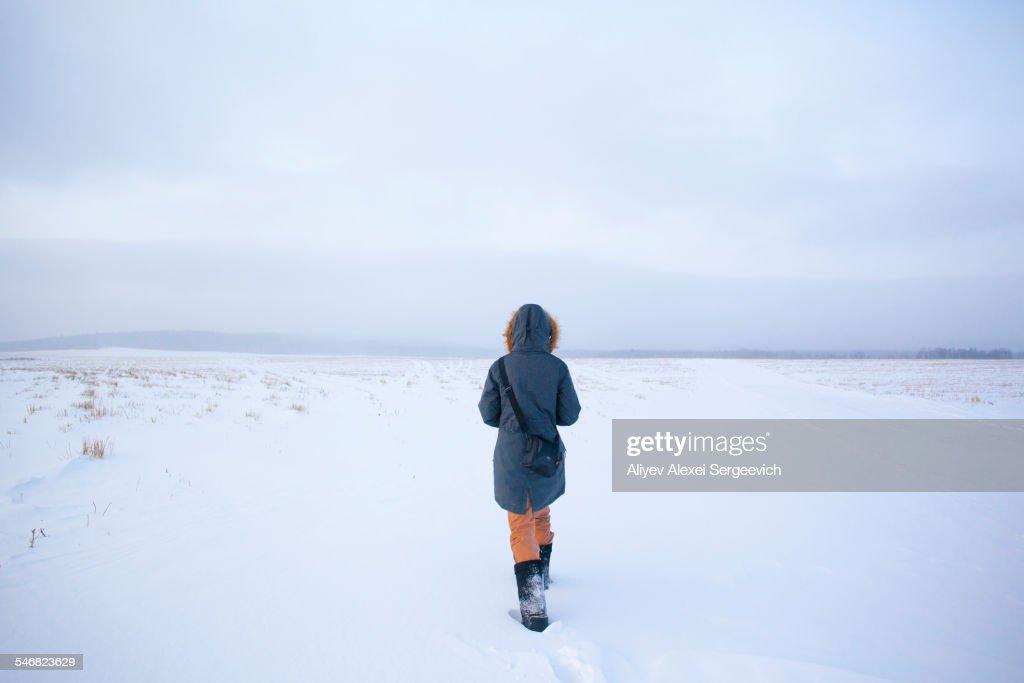 Caucasian woman walking in snowy field : Stock Photo