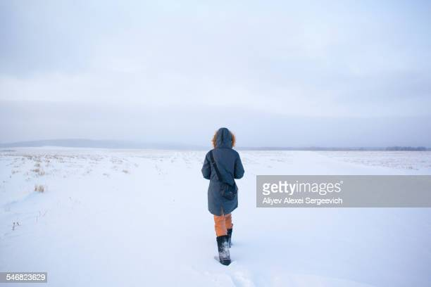 caucasian woman walking in snowy field - parka coat stock photos and pictures