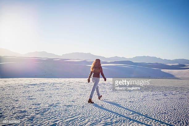 caucasian woman walking in white sands national park, new mexico, united states - winter coat stock pictures, royalty-free photos & images