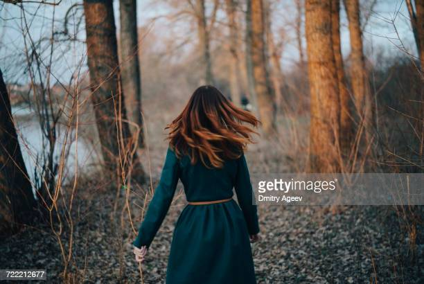 Caucasian woman walking near trees and river