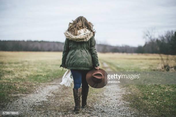 Caucasian woman walking on dirt path in rural field