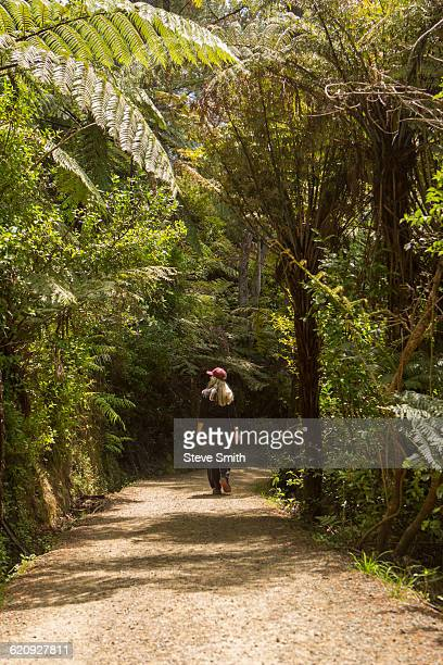 Caucasian woman walking on path in rural forest