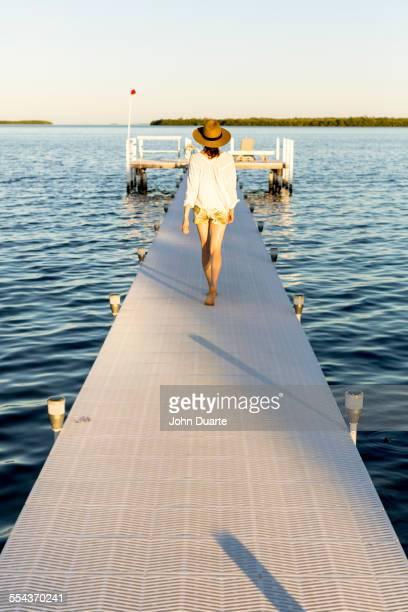 Caucasian woman walking on pier over water