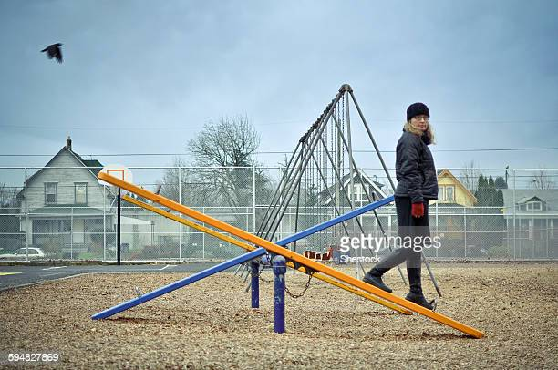 Caucasian woman walking on playground seesaw