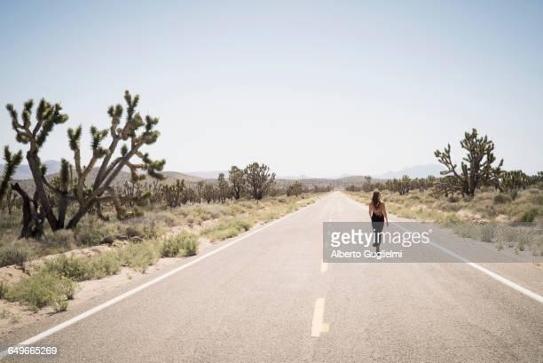 caucasian woman walking on remote desert road - nevada stock-fotos und bilder