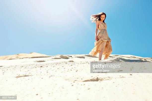 Caucasian woman walking on sand dune hill