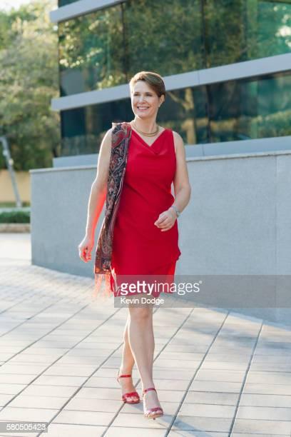 Caucasian woman walking on sidewalk
