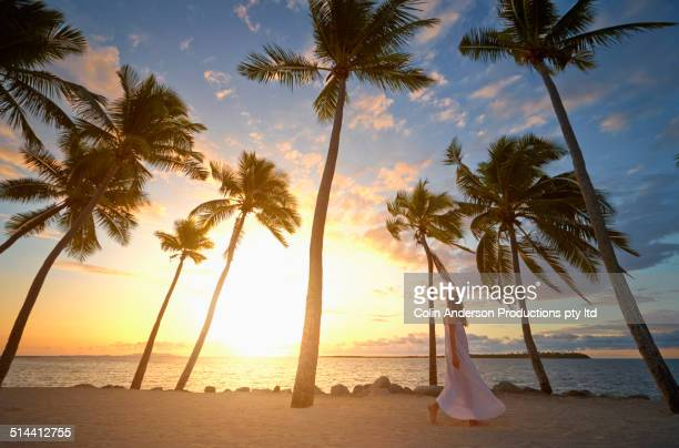 Caucasian woman walking on tropical beach