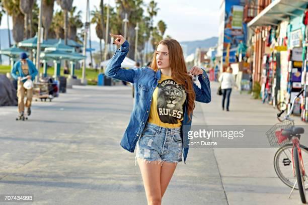Caucasian woman walking on Venice Beach sidewalk, Venice, California, United States