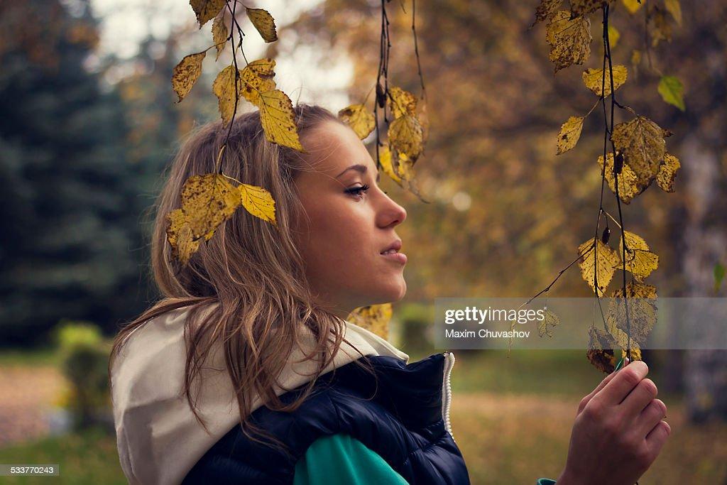Caucasian woman walking under autumn leaves on tree : Foto stock