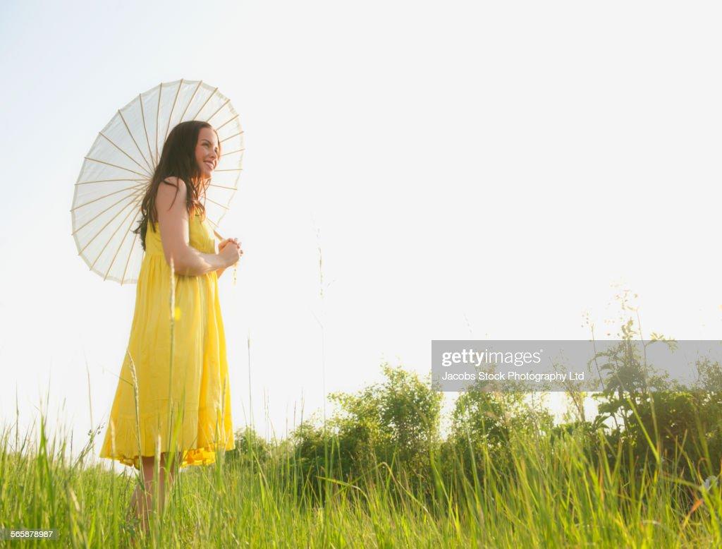 Caucasian woman walking under parasol in rural field : Stock Photo