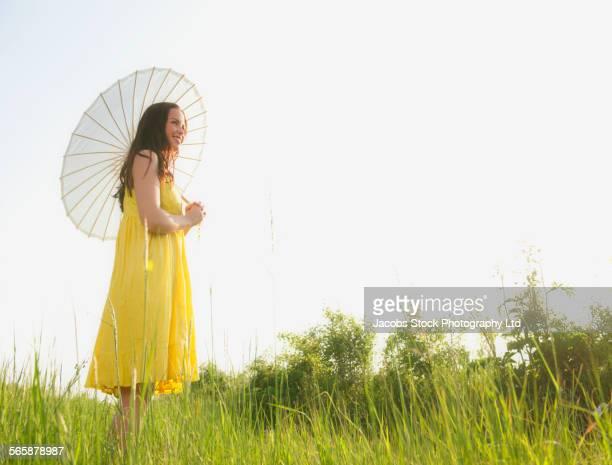 Caucasian woman walking under parasol in rural field