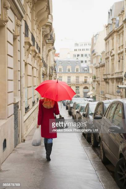 Caucasian woman walking under umbrella on city sidewalk