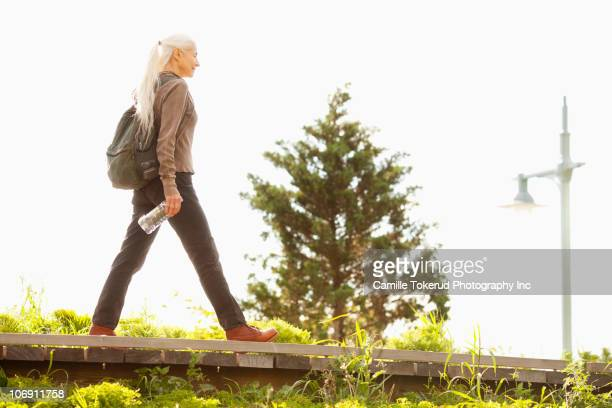Caucasian woman walking with backpack and bottled water