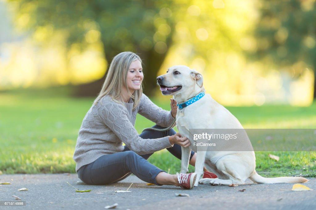 Caucasian woman walks her dog on beautiful summer evening in park : Stock Photo